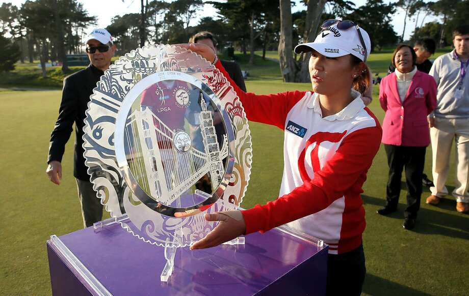 Lydia Ko picks up the champions trophy after her win of the 2015 the Swinging Skirts LPGA  Classic golf tournament at Lake Merced Golf Course in Daly City, Calif., on Sun. April 26, 2015. Photo: Michael Macor, The Chronicle