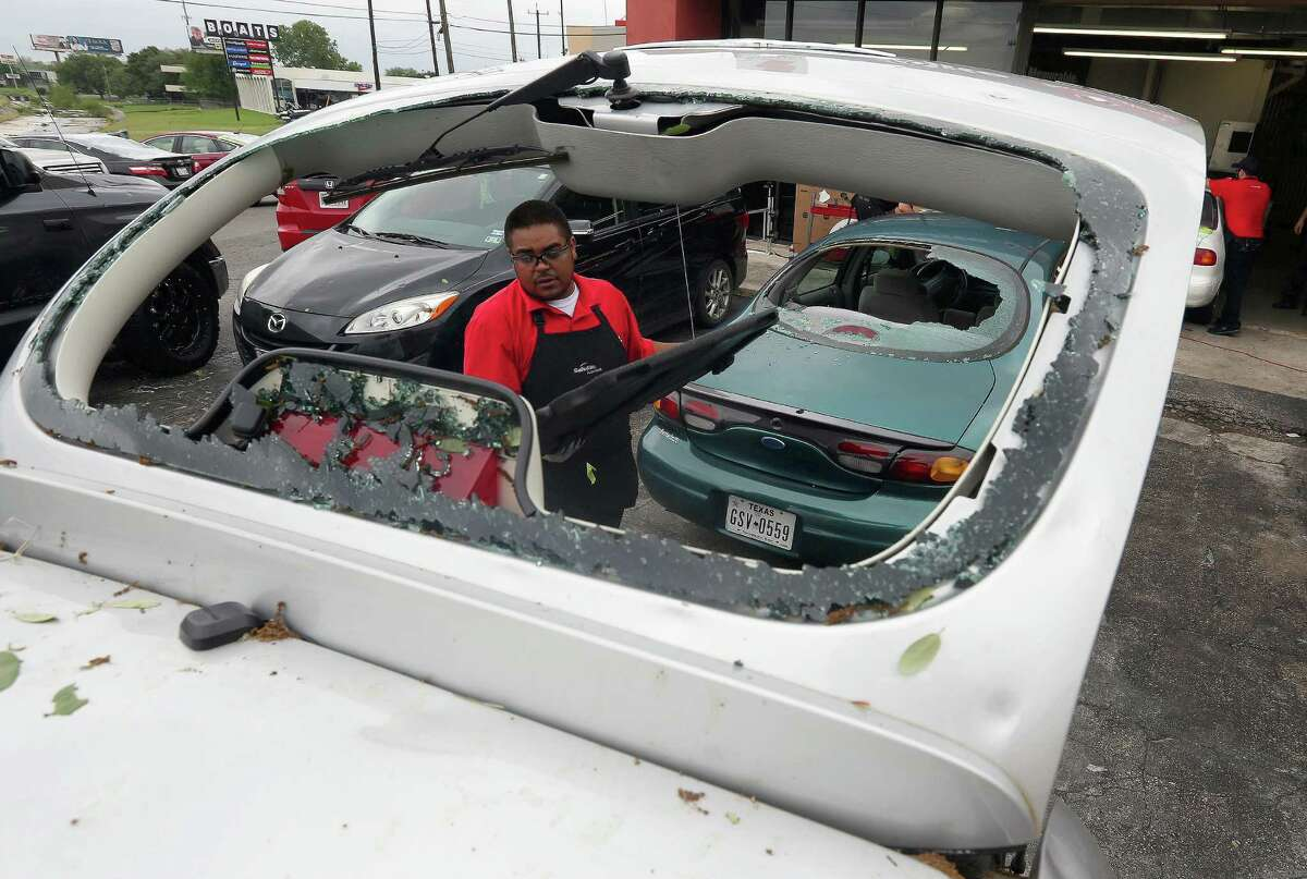 Safelite automotive glass repair company employee Erik White remove broken glass Wednesday, April 13, 2016 at the company's I-10 location after a widespread overnight hail storm broke windshields throughout large swaths of the city.
