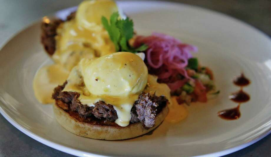 Barbacoa Benedict substitutes shredded beef cheek in place of the Canadian bacon of a traditional eggs Benedict. It's served with pickled red onions and pico de gallo. Photo: Kin Man Hui /San Antonio Express-News / ©2016 San Antonio Express-News