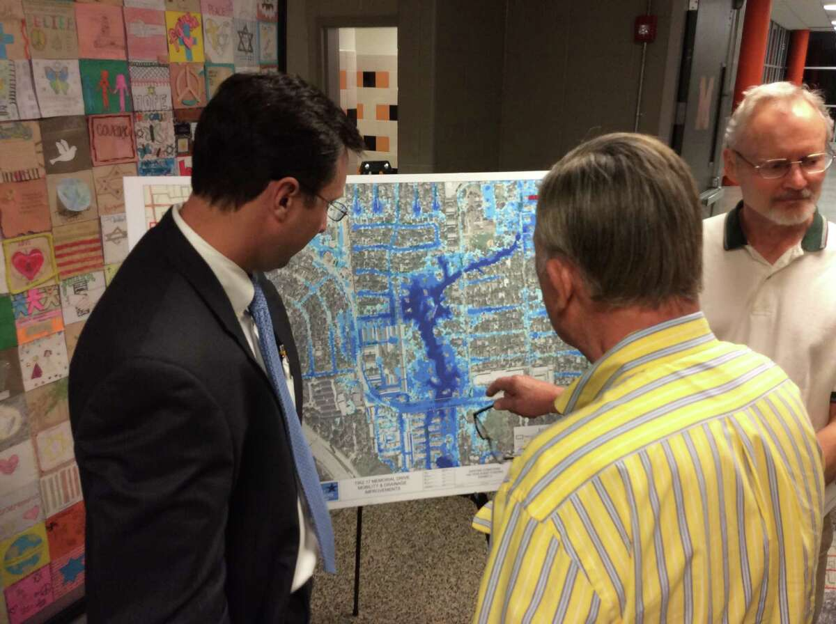Memorial-area residents visit with TIRZ 17 engineer Derek St. John, at left, to discuss drainage improvements that will occur when Memorial Drive is rebuilt from Beltway 8 to east of Tallowood. (Chronicle file photo)