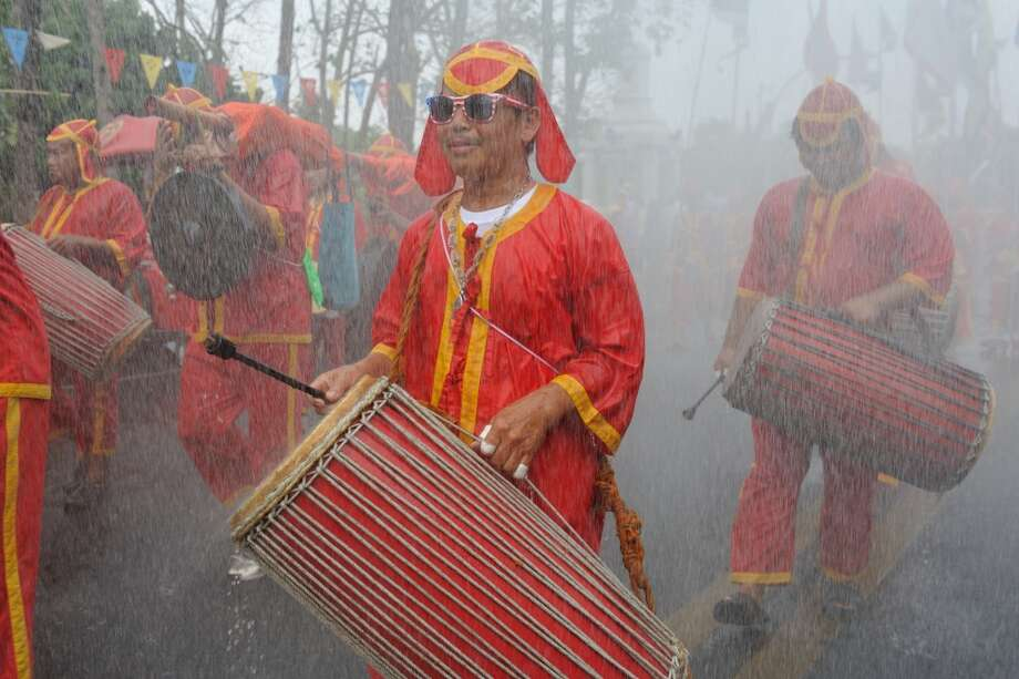 CHIANG MAI, THAILAND: Thai men dressed in traditional costumes play a traditional drums in a procession of Songkran festival at Tapae street.  Photo: LightRocket Via Getty Images