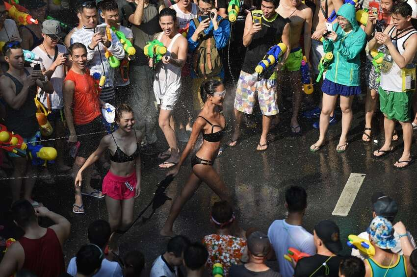 Bikini-clad women take part in water battles as people celebrate Songkran - the Thai new year - in Bangkok on April 13, 2016. Thais and tourists took to the streets on April 13 to drench each other in the mass water fight that marks the country's new year festival Songkran, as authorities attempted to crack down on alcohol, topless dancers and other