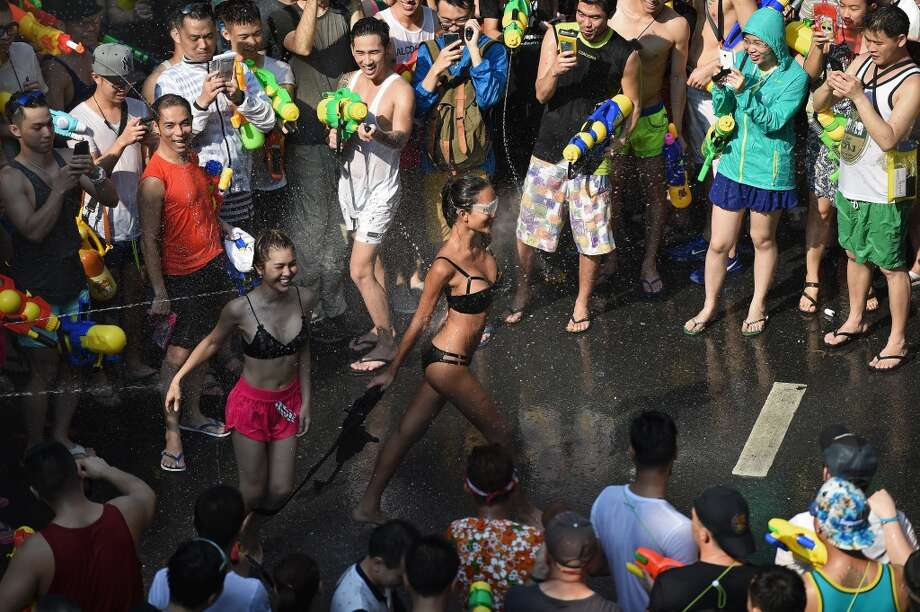 """Bikini-clad women take part in water battles as people celebrate Songkran - the Thai new year - in Bangkok on April 13, 2016.   Thais and tourists took to the streets on April 13 to drench each other in the mass water fight that marks the country's new year festival Songkran, as authorities attempted to crack down on alcohol, topless dancers and other """"indecencies"""". Photo: CHRISTOPHE ARCHAMBAULT, AFP/Getty Images"""