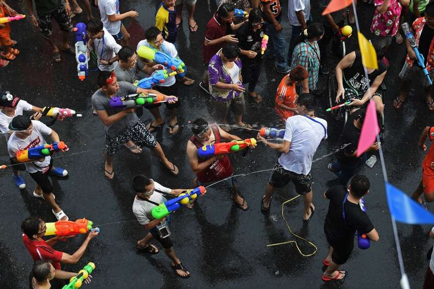 People take part in water battles as they celebrate Songkran - the Thai new year - in Bangkok on April 13, 2016. Thais and tourists took to the streets on April 13 to drench each other in the mass water fight that marks the country's new year festival Songkran, as authorities attempted to crack down on alcohol, topless dancers and other