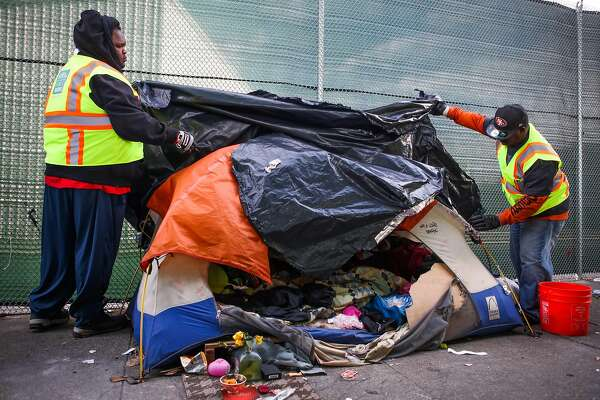 Department of Public Works employees look through an abandoned tent on Division Street before throwing it in the trash, in San Francisco, California, on Tuesday, March 1, 2016.
