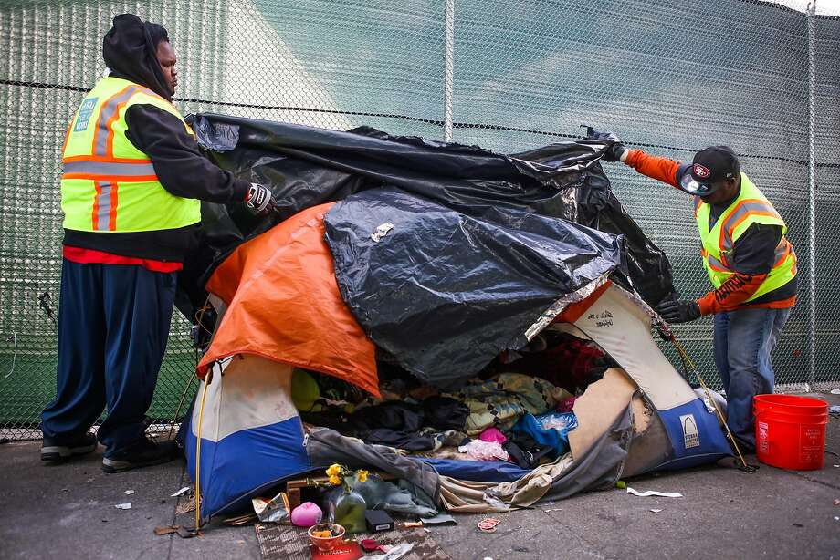 San Francisco Department of Public Works employees look through an abandoned tent on Division Street before throwing it in the trash in 2016. Photo: Gabrielle Lurie / Special To The Chronicle