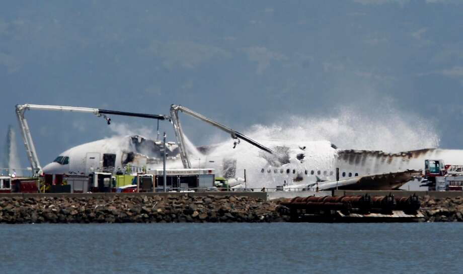Fire crews pour water and foam on an Asiana Airlines Boeing 777 that crashed while it was attempting to land from Seoul, South Korea at San Francisco International Airport in San Francisco, Calif. on Saturday, July 6, 2013. Photo: Paul Chinn, The Chronicle