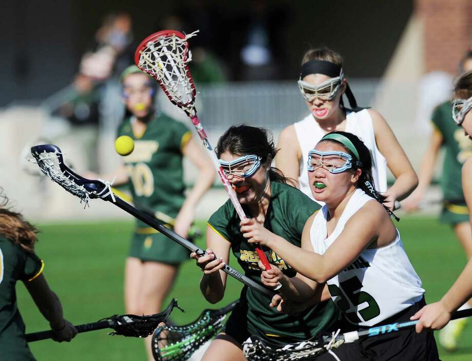 At left, Holly Johnson of Greenwich Academy's fights for a loose ball with Hamden Hall's Claire Pancoast (#25), right, during the girls high school lacrosse match between Greenwich Academy and Hamden Hall at Greenwich Academy, Greenwich, Conn., Wednesday, April 13, 2016. Greenwich Academy defeated Hamden Hall, 10-1. Photo: Bob Luckey Jr. / Hearst Connecticut Media / Greenwich Time