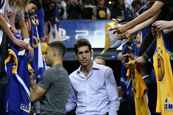 OAKLAND, CA - APRIL 01:  Golden State Warriors general manager Bob Myers walks past Stephen Curry #30 of the Golden State Warriors as Curry signs autographs before their game against the Boston Celtics at ORACLE Arena on April 1, 2016 in Oakland, California. NOTE TO USER: User expressly acknowledges and agrees that, by downloading and or using this photograph, User is consenting to the terms and conditions of the Getty Images License Agreement.  (Photo by Ezra Shaw/Getty Images)