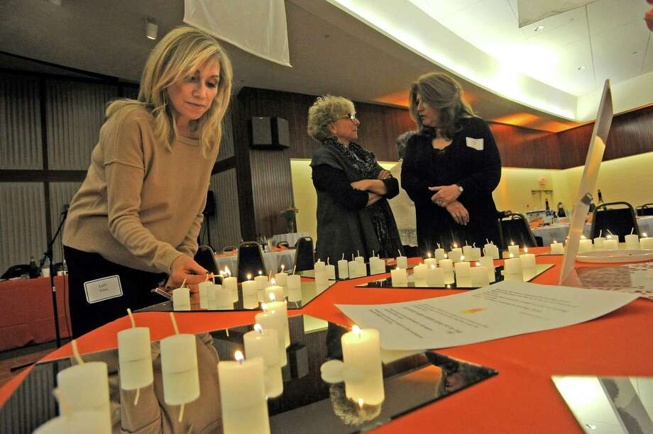Lori Tobin of Stamford, at left, lights a candle in honor and or in memory of a woman who has held an important place in her life. Tobin was one of  150 women who gathered together at Temple Beth El on April 13, 2016 to hold an intergenerational women's seder. The seder is a festive meal that celebrates the Jewish holiday of Passover, at which time Jews around the world retell the story of their liberation from slavery in ancient Egypt that is written about in the biblical book of Exodus. Photo: Matthew Brown / Hearst Connecticut Media / Stamford Advocate
