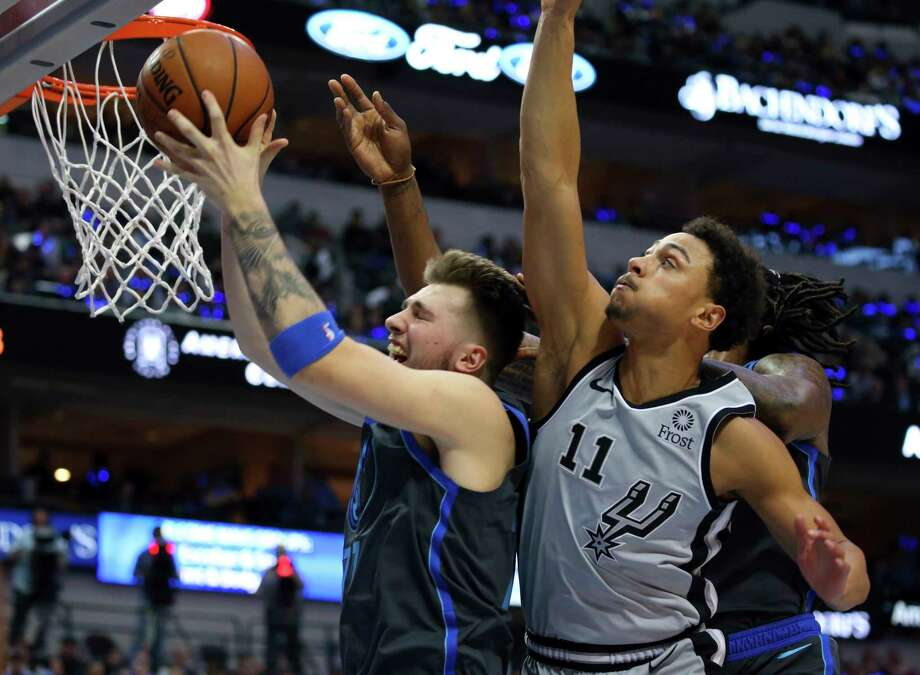 Dallas Mavericks forward Luka Doncic (77) pulls down a rebound against San Antonio Spurs guard Bryn Forbes (11) in the first half of an NBA basketball game, Wednesday, Jan. 16, 2019, in Dallas. (AP Photo/Richard W. Rodriguez) Photo: Richard W. Rodriguez, Associated Press / Copyright 2019 The Associated Press. All rights reserved.
