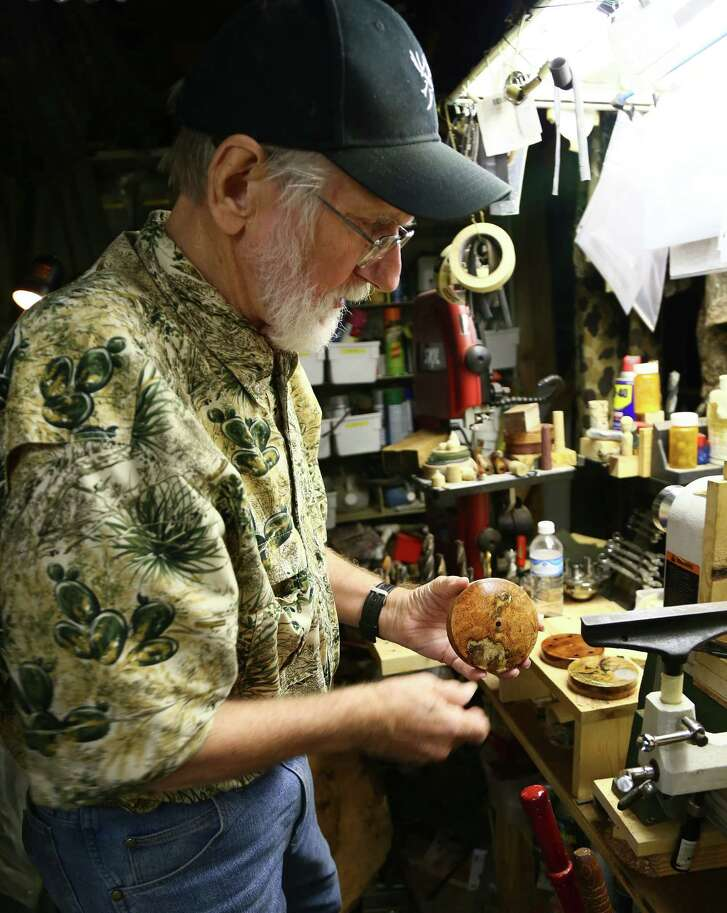 Bill Crowell inspects the burled wood he's using to build a custom turkey call in his shop in Humble. Crowell is one of the few makers of turkey calls in Texas.