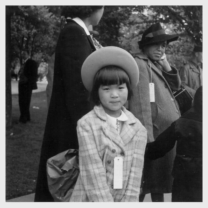 Dressed in her best clothes, Mae Yanagi, 7, waits with her pregnant mother, Kinuye Yanagi, right, to be bused to housing in the Tanforan Assembly Center by the War Relocation Authority. The Yanagi family spent several months in a horse stall at Tanforan before being sent to the Topaz Internment Camp in the Utah desert. Hayward, California. Photograph by Dorothea Lange.5/ 8/ 42