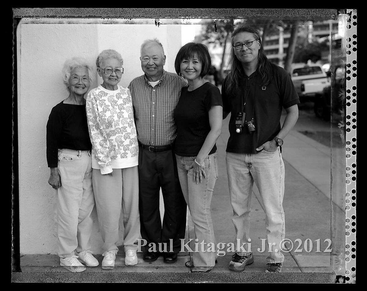 Nisei, second generation Japanese Americans, Agnes Eiko Kitagaki (Takahashi) Poston Internment camp, Kimiko Wong (Kitagaki), and her brother, Paul Kiyoshi Kitagaki, (Topaz Internment Camp) with their Sansei, third generation Japanese America children, Sharon Young (Wong) and Paul Kitagaki Jr. stand outside of the building on 12th and Oak Streets where Kimiko and Kiyoshi were photographed by Dorothea Lange before they boarded a bus in May of 1942 for the Tanforan Assembly center and then Topaz Interment camp. Photographed September, 18, 2005.
