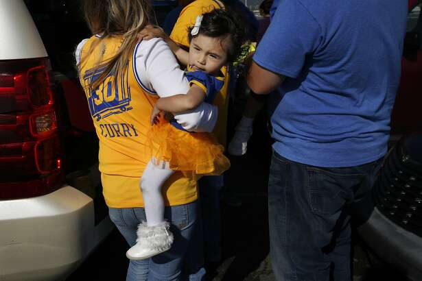Lupe Caballero holds her daughter Katelyn, 15 mo., as she hangs out with family members, including her brother-in-law Jordan Caballero, right, before the Warriors vs. the Memphis Grizzlies game outside the Oracle Arena April 13, 2016 in Oakland, Calif.