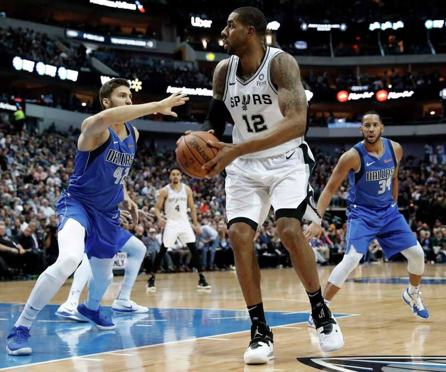 San Antonio Spurs center LaMarcus Aldridge (12) works against Dallas Mavericks forward Maximilian Kleber (42) and Devin Harris (34) for a shot attempt during the first half of an NBA basketball game in Dallas, Tuesday, March 12, 2019. (AP Photo/Tony Gutierrez) Photo: Tony Gutierrez, Associated Press / Copyright 2019 The Associated Press. All rights reserved.
