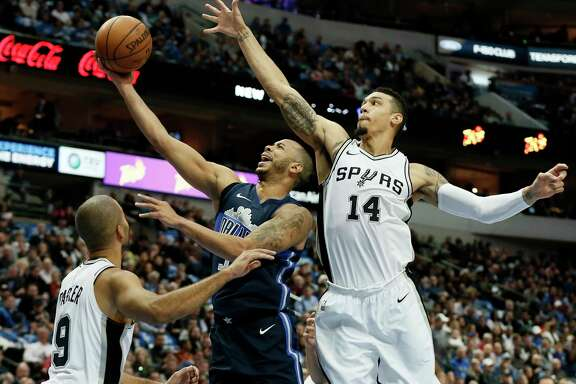 San Antonio Spurs guard Tony Parker , left, of France and Danny Green, right,  defend as Dallas Mavericks' Devin Harris, center, goes up for a shot in the first half of an NBA basketball game,Tuesday, Dec. 12, 2017, in Dallas. (AP Photo/Tony Gutierrez)