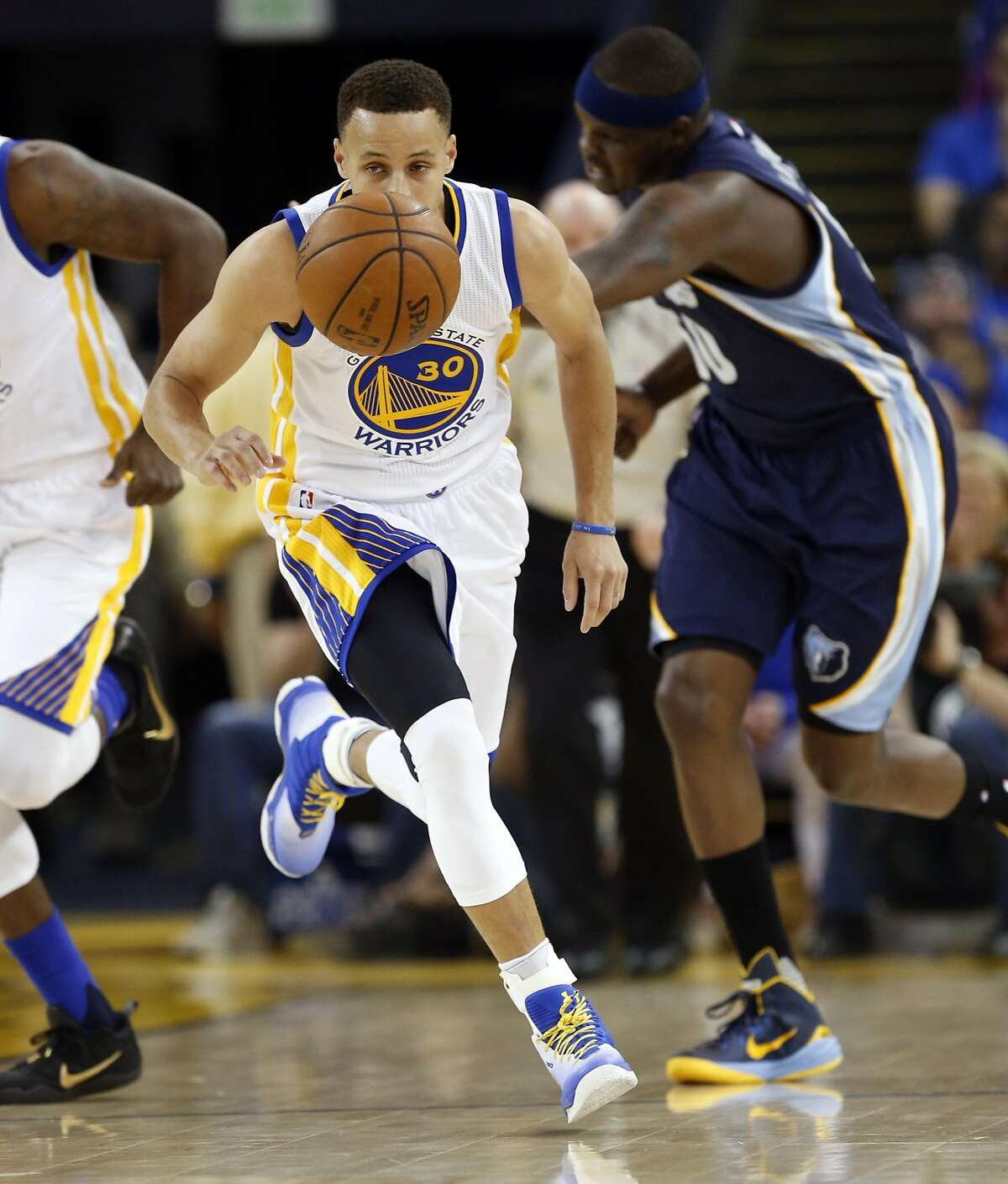 Golden State Warriors' Stephen Curry heads up court leaving Memphis Grizzlies' Zach Randolph behind in 1st quarter during NBA game at Oracle Arena in Oakland, Calif., on Wednesday, April 13, 2016.