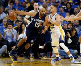 Golden State Warriors' Stephen Curry defends against Memphis Grizzlies' Vince Carter in 1st quarter during Warriors' 125-104 win in NBA game at Oracle Arena in Oakland, Calif., on Wednesday, April 13, 2016.