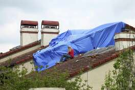 """A worker protects a roof at The Village at Woodlake in this April 13 photo. A severe hailstorm affected the area April 12, damaging houses throughout the city's northeast and northwest sides. National Weather Service meteorologist Jason Runyen said the largest recorded size of hail came when the storms were near Helotes. The hail measured 3.5 inches in diameter. """"That's basically the size of a tea cup and grapefruit just south of Helotes,"""" Runyen said."""