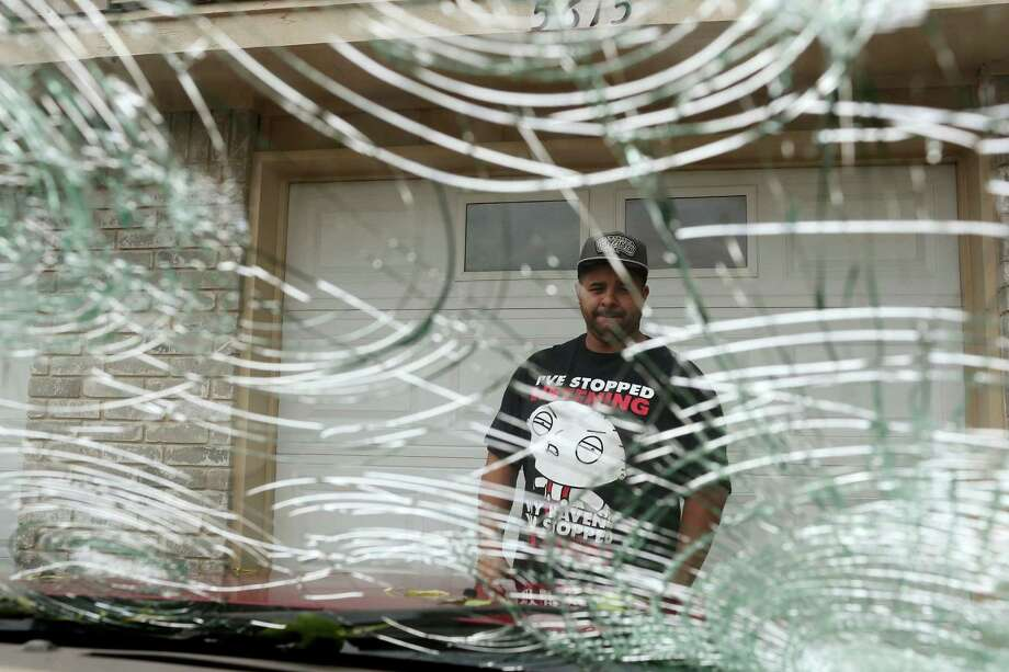 """Rodney Rodriguez checks the damage to his 2008 Ford Escape in theWoodlake neighborhood on the city's northeast side, Wednesday, April 13, 2016. A severe hailstorm affected the area Tuesday night damaging houses throughout the city's northeast and northwest sides. National Weather Service meteorologist Jason Runyen said the largest recorded size of hail came when the storms were near Helotes. The hail measured 3.5 inches in diameter. """"That's basically the size of a tea cup and grapefruit just south of Helotes,"""" Runyen said. Photo: JERRY LARA, Staff / San Antonio Express-News / © 2016 San Antonio Express-News"""