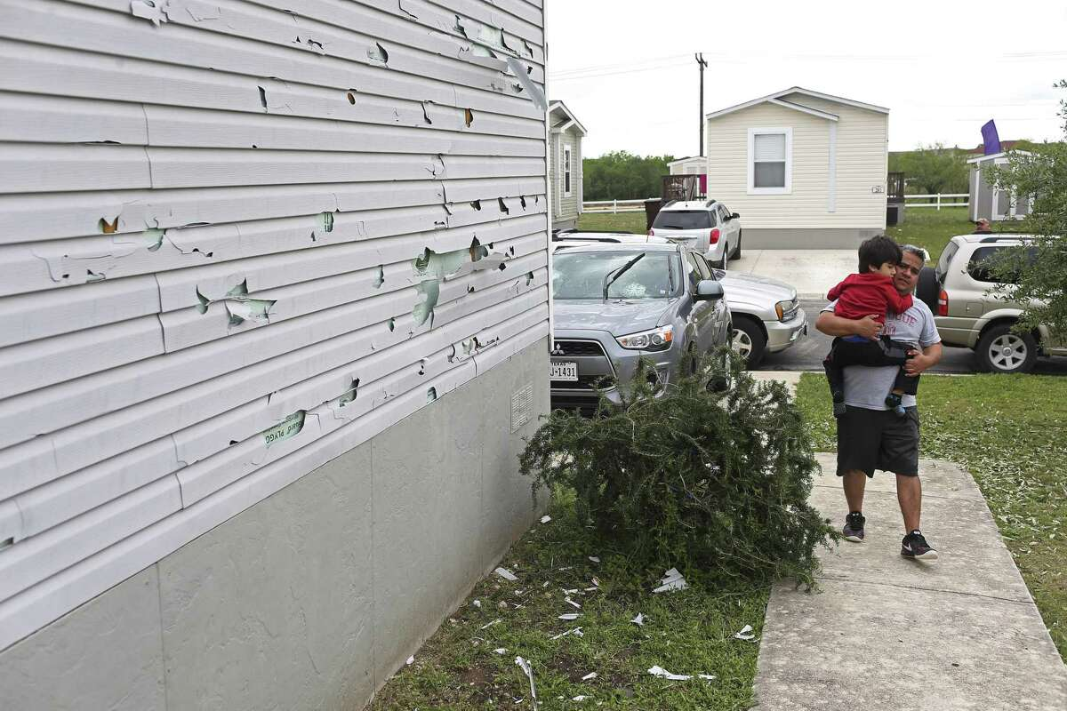 Everardo Rosales, 30, carries his son, Emiliano, 5, at their mobile home at the Woodlake Estates in the citys northeast side on April 13, 2016. A severe hailstorm affected the area the previous day, damaging houses throughout the city's northeast and northwest sides. National Weather Service meteorologist Jason Runyen said the largest recorded size of hail came when the storms were near Helotes. The hail measured 3.5 inches in diameter.