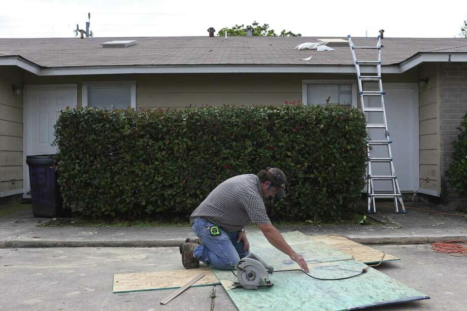 Handyman David Beavers cuts plywood to secure broken skylights at duplexes in Woodlake neighborhood in the city's northeast side after a severe hailstorm on April 12, 2016. Photo: JERRY LARA /San Antonio Express-News / © 2016 San Antonio Express-News