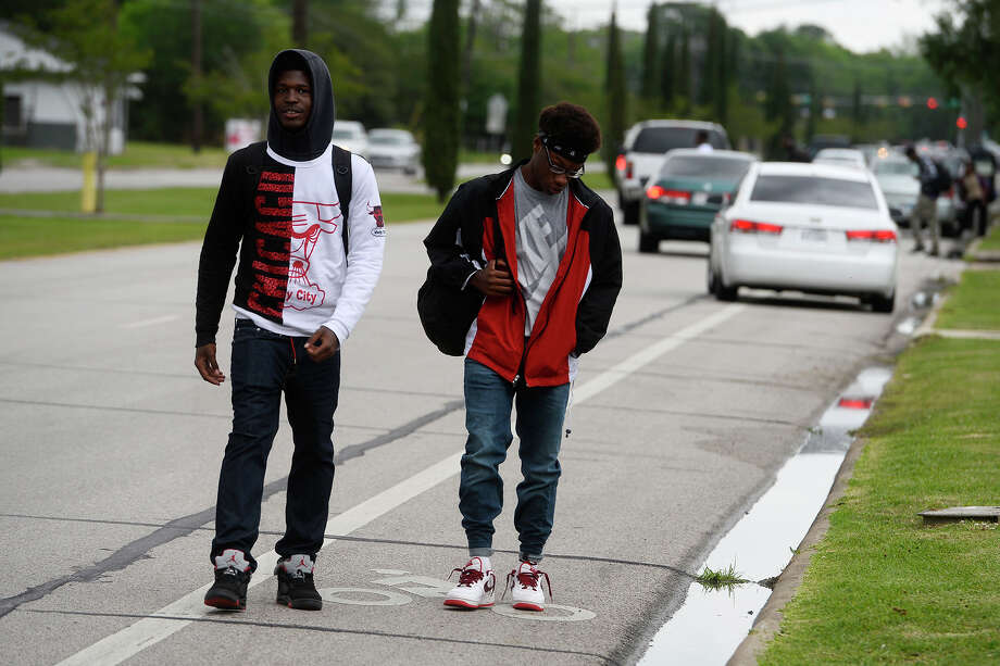 Anthony Jones, left, and Darrius Stevens walk in the bike lane along Fannett Road on their way home after school on Wednesday afternoon. The city is considering building sidewalks in the area.  Photo taken Wednesday 4/13/16 Ryan Pelham/The Enterprise Photo: Ryan Pelham / ©2016 The Beaumont Enterprise/Ryan Pelham