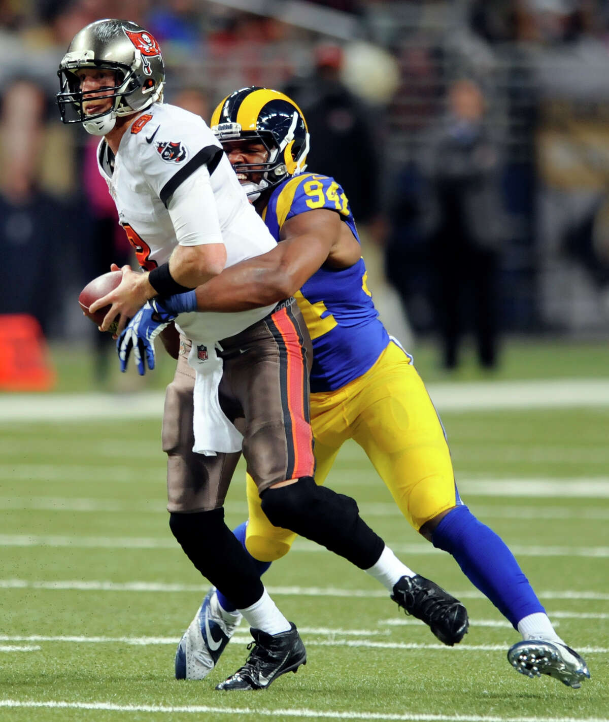 Tampa Bay Buccaneers quarterback Mike Glennon, left, is sacked by St. Louis Rams defensive end Robert Quinn for a 9-yard loss during the second quarter of an NFL football game on Sunday, Dec. 22, 2013, in St. Louis. (AP Photo/L.G. Patterson)