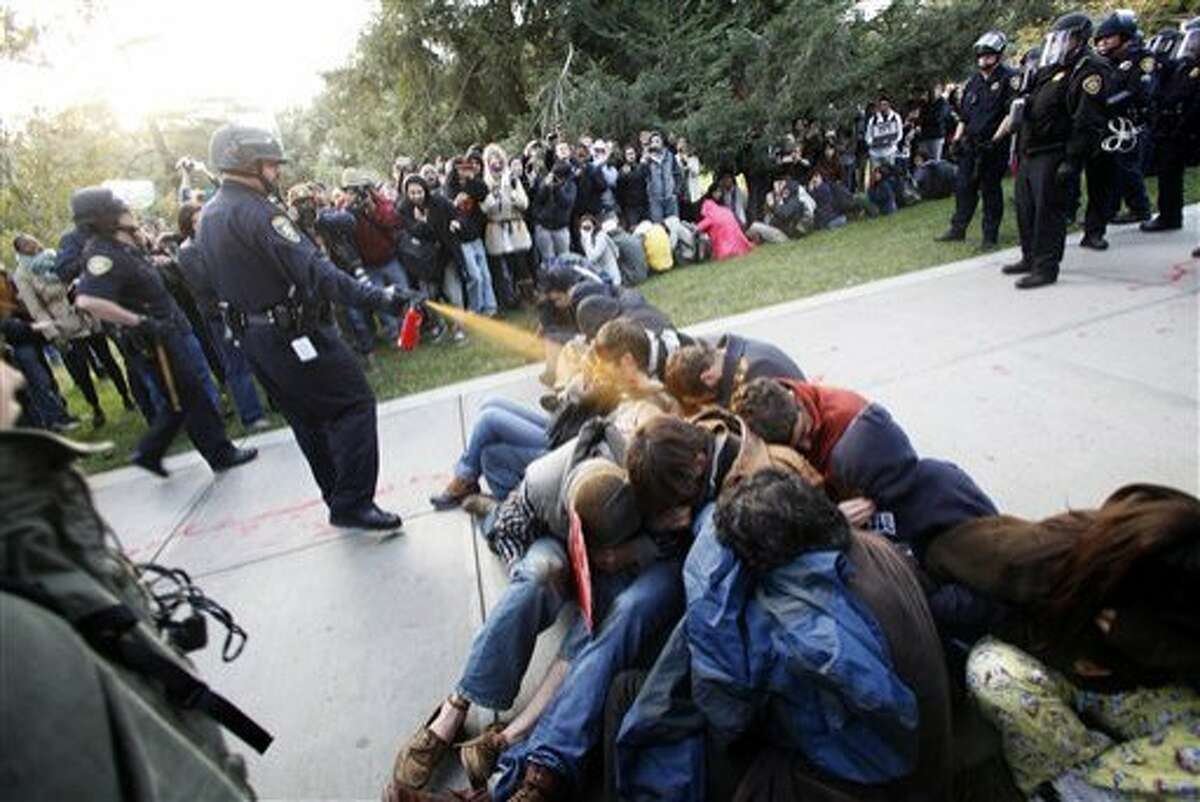 FILE - In this Nov. 18, 2011 file photo, University of California, Davis Police Lt. John Pike uses pepper spray to move Occupy UC Davis protesters while blocking their exit from the school's quad in Davis, Calif. The University of California has agreed to pay nearly $1 million to settle a lawsuit filed by demonstrators who were pepper-sprayed in the face during an Occupy protest, an incident that became a defining moment in the short-lived movement against economic inequality. (AP Photo/The Enterprise, Wayne Tilcock, File)