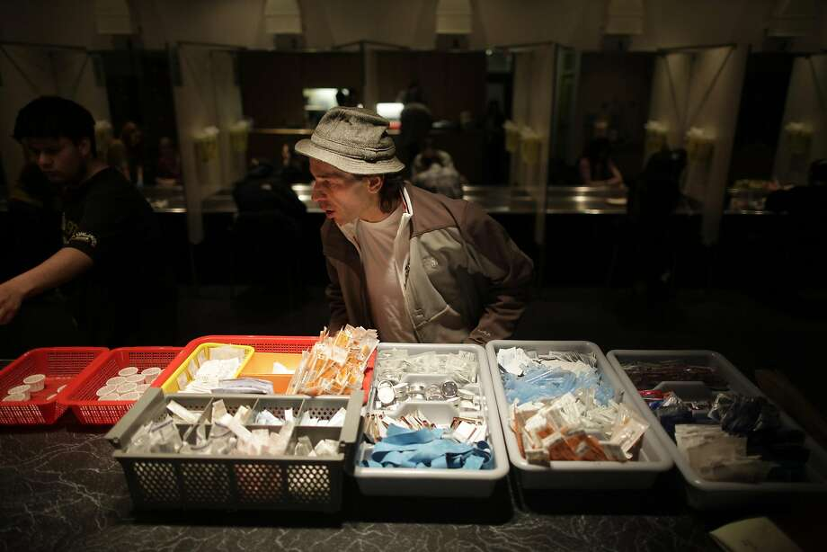 Lawrence Golden-Brooks examines syringes, tourniquets and sterile water at the Insite center in 2010. Photo: ED OU, NYT