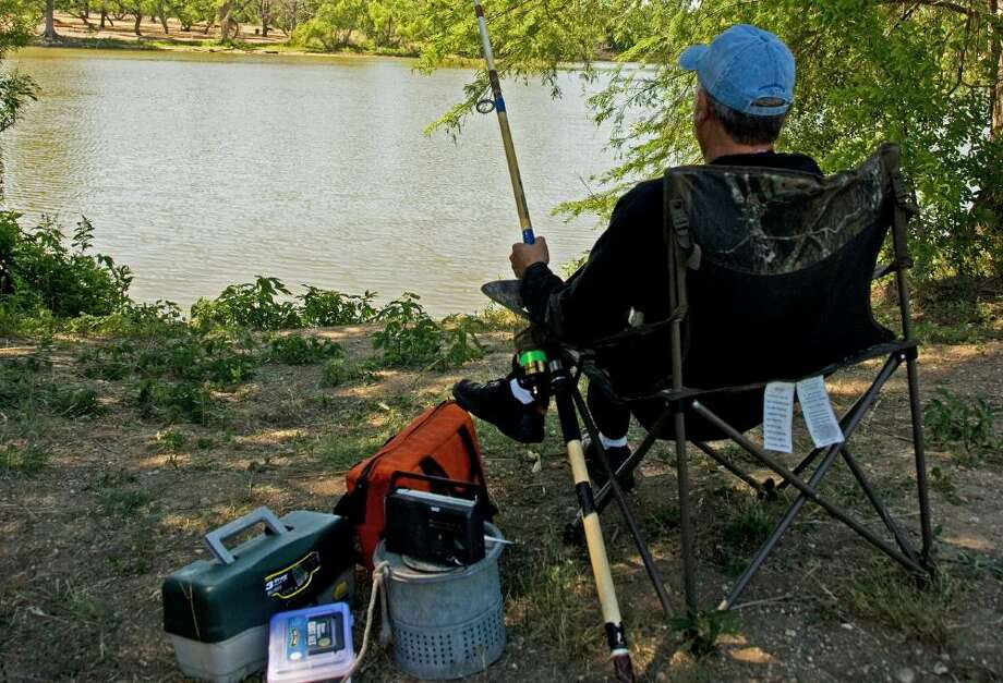 Fishing for catfish at the Neighborhood Fishin' Program lakes can be a relaxing affair, as this angler sitting in the shade at Southside Lions Park demonstrates. Photo: John Goodspeed / For The Express-News / John Goodspeed / For The Express-News