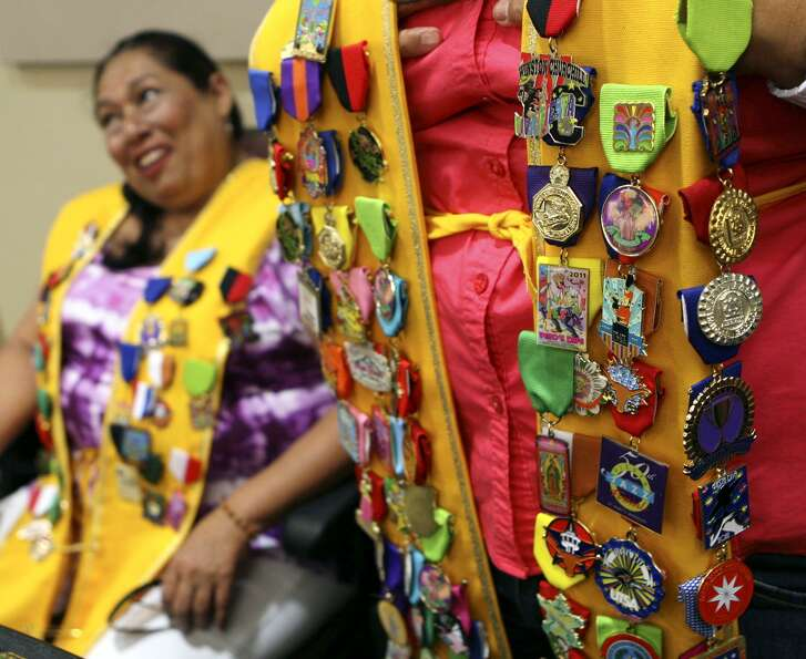 Minerva Ray wears her homemade sash in 2013 with about 50 Fiesta medals on it as she and Cynthia Rodriguez (left) wait for King Antonio and other Fiesta dignitaries to make their annual pre-Fiesta visit to the Commissioners Court. The two were hoping to add to their collection.
