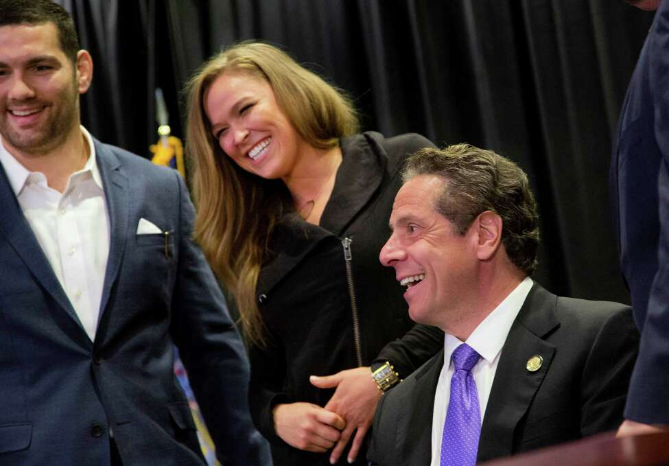 Gov. Andrew Cuomo, right, smiles with UFC athletes Chris Weidman, left, and Ronda Rousey after signing into law a bill that will allow professional mixed martial arts in New York, Thursday, April 14, 2016. Cuomo said at the signing ceremony at Madison Square Garden that the fights will boost the economy. New York was the last U.S. state to prohibit the bouts. (AP Photo/Mark Lennihan)