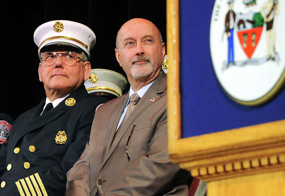 Troy Fire Chief Thomas Garrett, left, and Troy Mayor Patrick Madden listen as Albany Fire Chief Warren Abriel, Jr. speaks during a joint graduation ceremony for the Albany, Troy and Watervliet Fire Departments at the Palace Theatre on Thursday, April 14, 2016 in Albany, N.Y.  (Lori Van Buren / Times Union) Photo: Lori Van Buren / 10036190A
