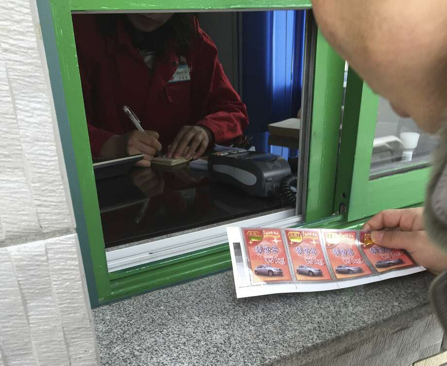 A customer uses coupons to buy gasoline at a station in Pyongyang, North Korea, in February. Photo: Eric Talmadge, AP