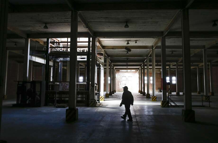 Caretaker Willie Agnew walks through the main warehouse building at the old Point Molate Fuel Department of the Naval Supply Center. Photo: Michael Macor, The Chronicle