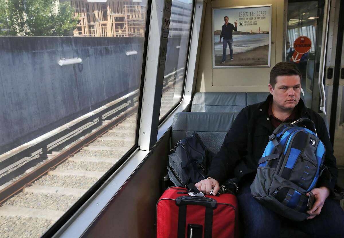 Matt Worley from Nashville holds onto his bags as he rides the SFO-bound BART train April 14, 2016 in San Francisco, Calif.