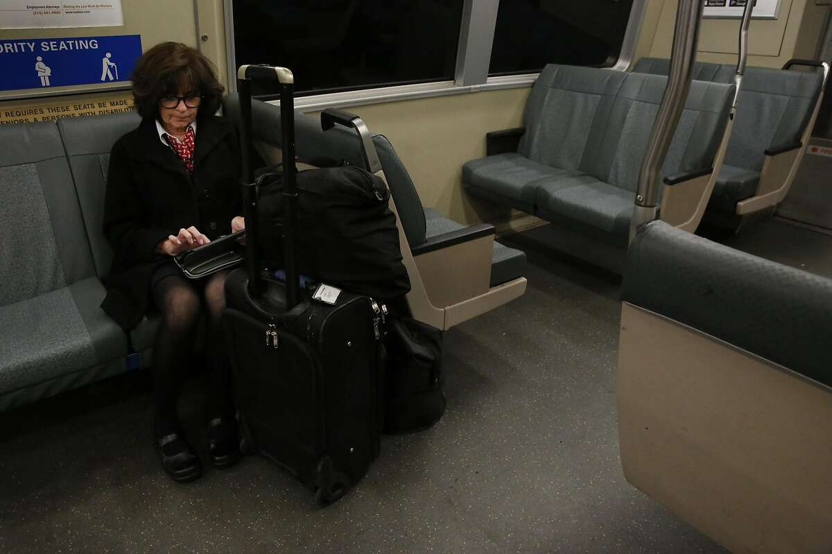 Cheryl Willner, who is a flight attendant, plays a game on her tablet as she sits with her three large bags in one seat space on the SFO-bound BART train April 14, 2016 in San Francisco, Calif. Willner says she is very conscious of taking up space.