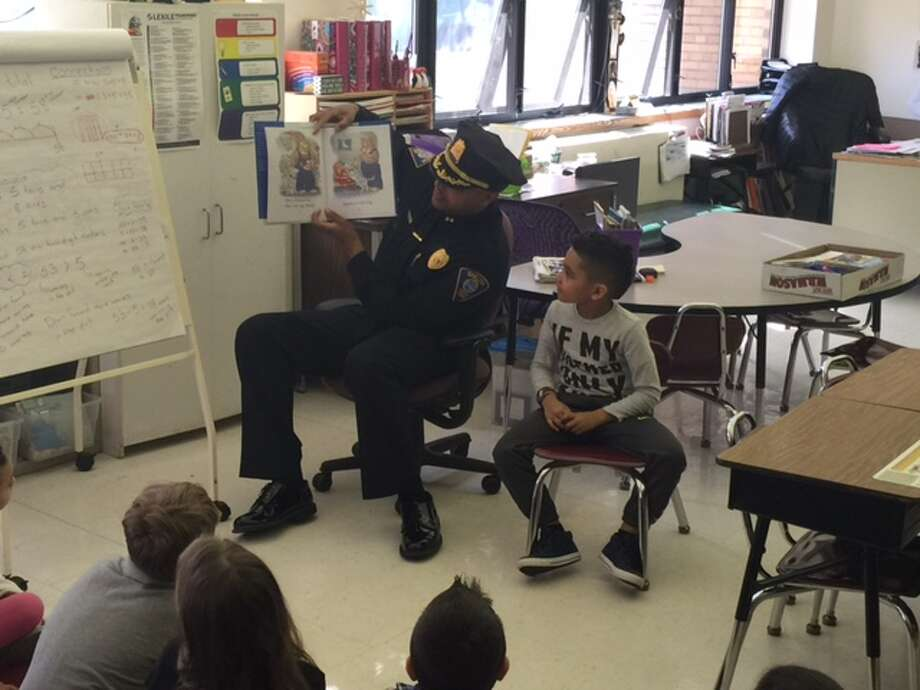 Shelton Police Chief Shawn Sequeira sits with his son, Shawn Jr. as he reads to Donna Centopani's first grade class at Sunnyside School during Read Across the Valley last week Photo: / Contributed Photo