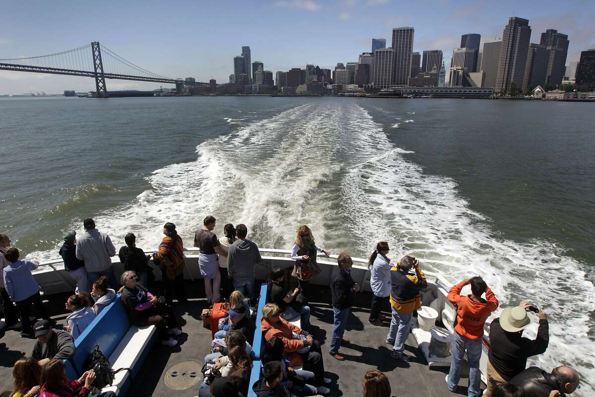 Passengers aboard the San Francisco ferry take photos of the city skyline from the fantail Friday August 13, 2010. The Golden Gate Ferry system will celebrate their 40th anniversary serving Fan Francisco, Larkspur and Sausalito this weekend.