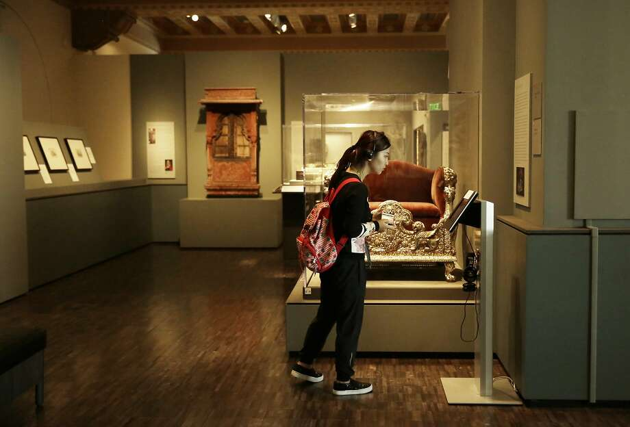 Run Yan of Fremont reads a multimedia display in a gallery at the Asian Art Museum. Photo: Lea Suzuki, The Chronicle