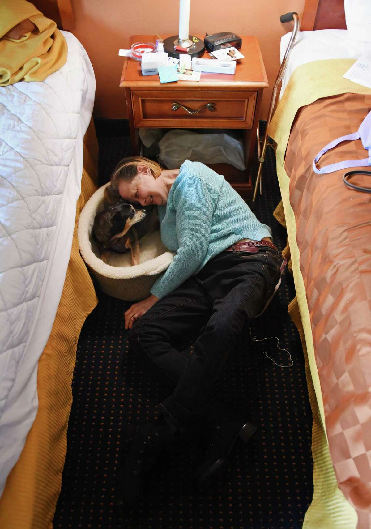 Denise Sadowsky cuddles with her dog, Cheeky, between hotel beds in her temporary residence at the Americas Best Value Inn in Stamford.