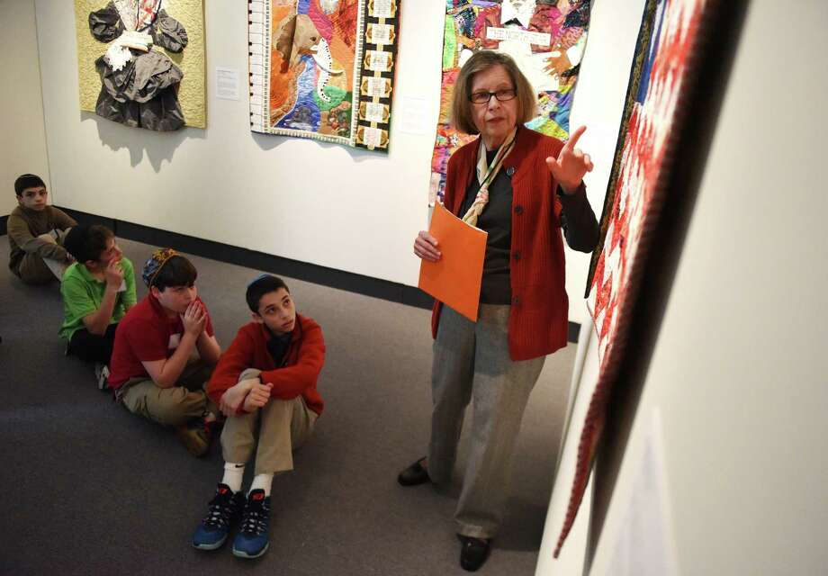 """Yvette Kahn, a docent at the Bruce Museum in Greenwich, leads a tour of the exhibition """"And Still We Rise: Race, Culture and Visual Conversations,"""" as Carmel Academy seventh-graders, from left, Matthew Bier, Jordan Sprecher, Daniel Kesler, and Seth Bier, listen and watch on Wednesday. Photo: Tyler Sizemore / Hearst Connecticut Media / Greenwich Time"""