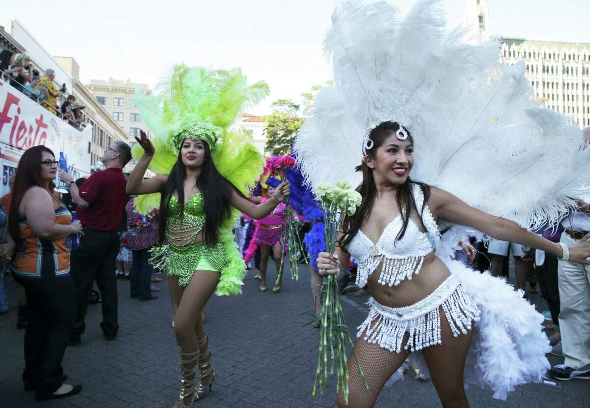Jessica Patino (in white), dance director, leads Samba Vida dancers in the flower parade as the official opening of Fiesta 2016 in front of the Alamo on April 14, 2016.
