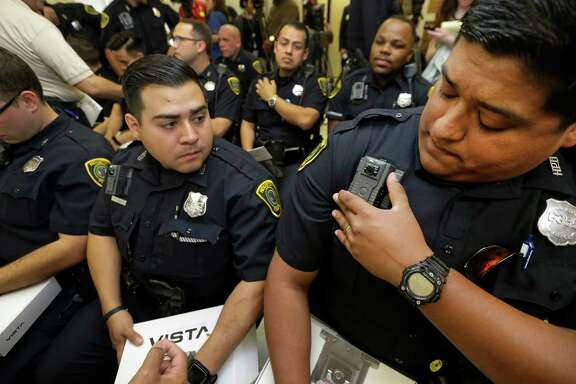 Houston Police officers T. R. Huerta, left, and J. C. Elizondo adjust their body cameras during an April 2016 news conference at HPD Central Patrol Station. About 200 officers received cameras, the first wave of outfitting 4,100 officers over 12-18 months.