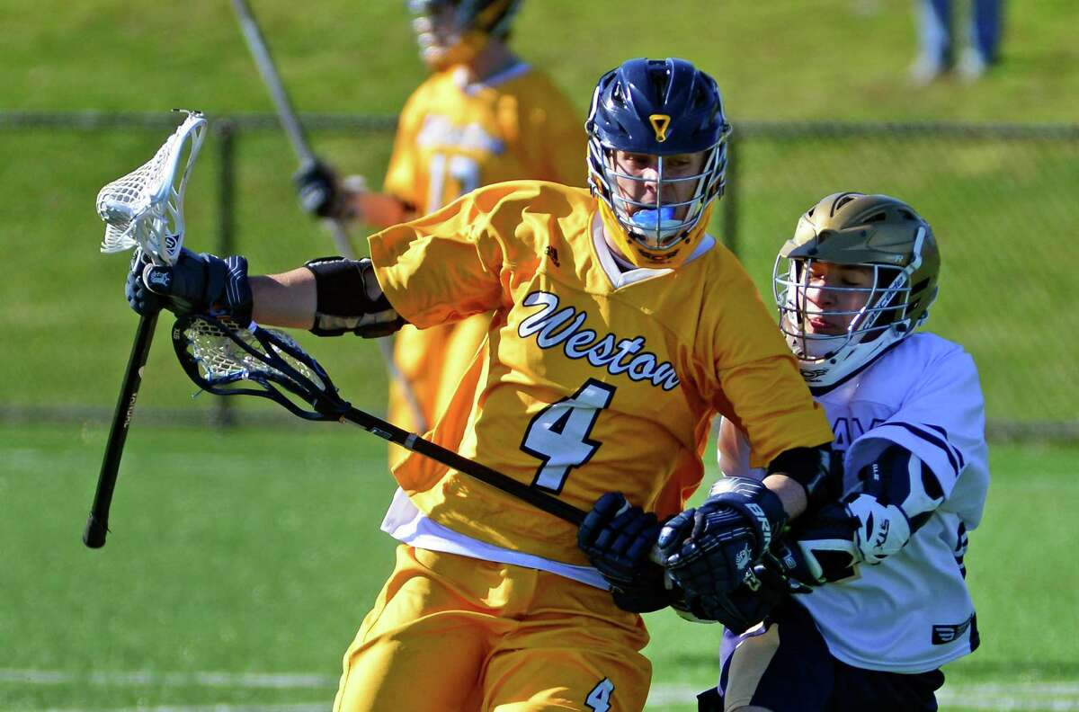 Weston's Alexander Fruhbeis drives towards the goal as Notre Dame of Fairfield's Trevor Sabia defends during boys lacrosse action in Bridgeport, Conn., on Thursday Apr. 14, 2016.