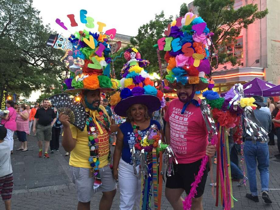 "Uriel Diaz, Maria Vega & John Paul Diaz spent 5 hours making their hats. ""We love Fiesta!"" Photo: Diana Fuentes, San Antonio Express News"
