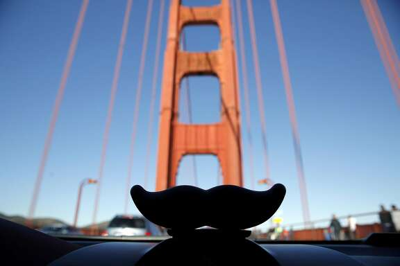 A Lyft mustache on a car dashboard in front of the Golden Gate Bridge near San Francisco, California, on Tuesday, Dec. 29, 2015.