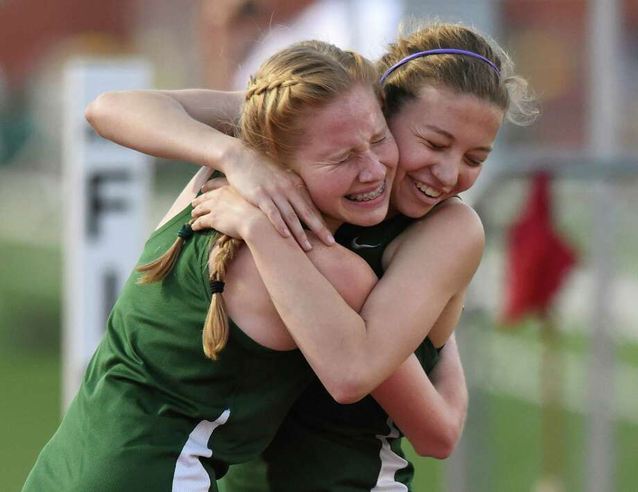 Alison Hepp, right, winner of the women's 1600 meter run, is embraced by Reagan teammate Anna King during the high school District 26-6A track and field championships at Heroes Stadium on Thursday, April 14, 2016. Photo: Billy Calzada, Staff / San Antonio Express-News / San Antonio Express-News